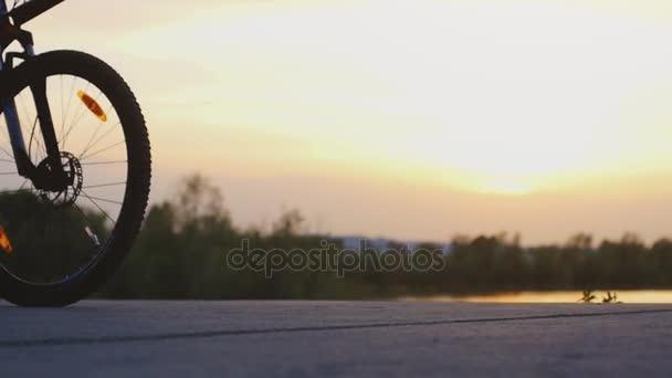 Muž, Cyklistika bycycle na silnici poblíž jezera během krásný západ slunce v pomalém pohybu. 1920 × 1080