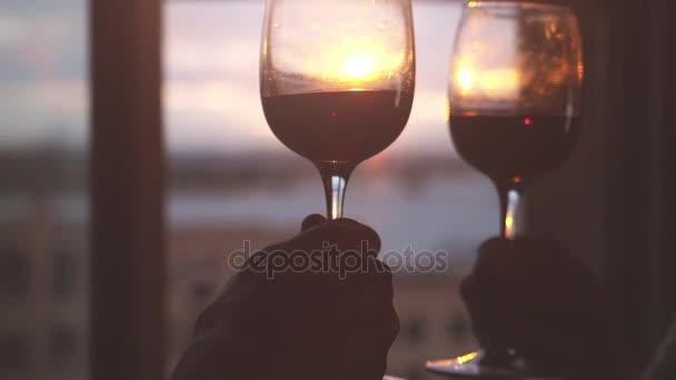 Dvě sklenky vína jsou kresleny navzájem pozadí okna s Městská krajina při západu slunce v pomalém pohybu. 1920 × 1080