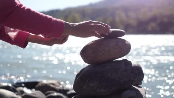Female hands putting pebble stack next to the mountain river in slow motion. 3840x2160