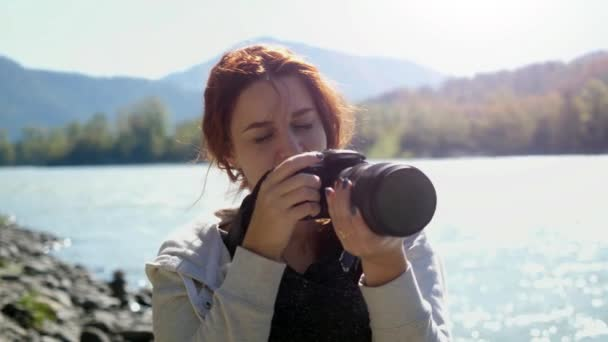 Beautiful woman with red hair photographer taking photo using professional camera outdoors on hike. Female hiker taking pictures outside living outdoor lifestyle in nature landscape. 3840x2160