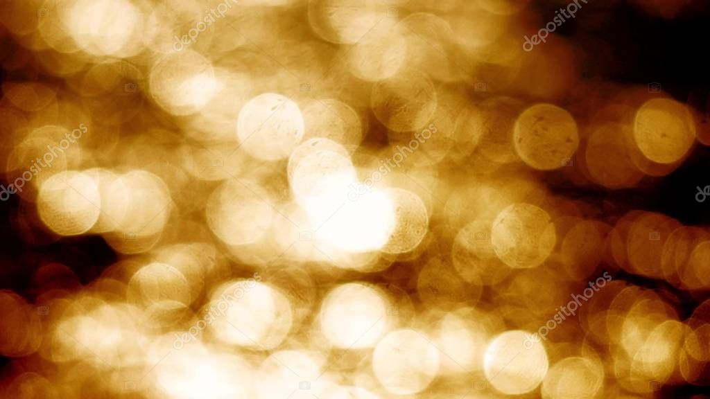 Beautiful gold abstract glittering lights bokeh background. Glistening and shimmering ocean surface at sunset