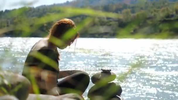 Young woman with red hairs relaxing putting pebble stack next to the mountain river. 3840x2160