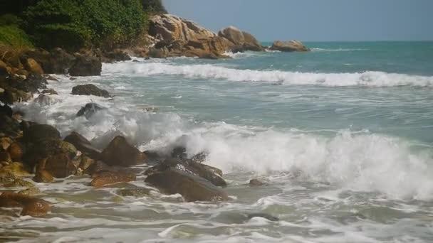 Mořské vlny narážející kamenité pláži v pomalém pohybu. 1920 × 1080