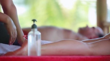 Close up of young woman lies in spa saloon on the tropical beach. Massage therapist doing legs oil massage. 1920x1080