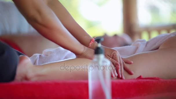Frau liegt im Wellness-Salon am tropischen Strand. Massage-Therapeuten Hände Beine Öl zu tun. 1920 x 1080