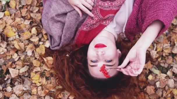 Krásná mladá zamyšlená žena s rudými vlasy leží nad suché listí v podzimním lese ve zpomaleném filmu. 3840 x 2160