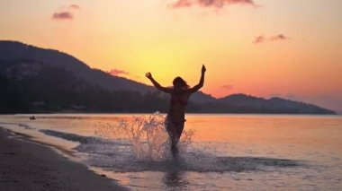Happy brunette young woman running in tropical beach at amazing sunset in slow motion. 1920x1080