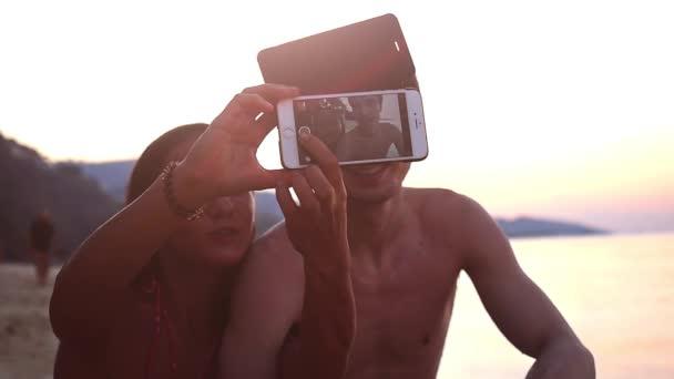 Dva nejlepší přátelé s selfie s mobilním telefonem během krásný západ slunce na tropické pláži. Zpomalený pohyb. HD, 1920 × 1080.