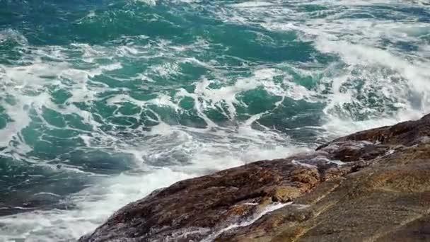 Velké vlny zřítilo na kamenité pláži ve zpomaleném filmu. 1920 × 1080