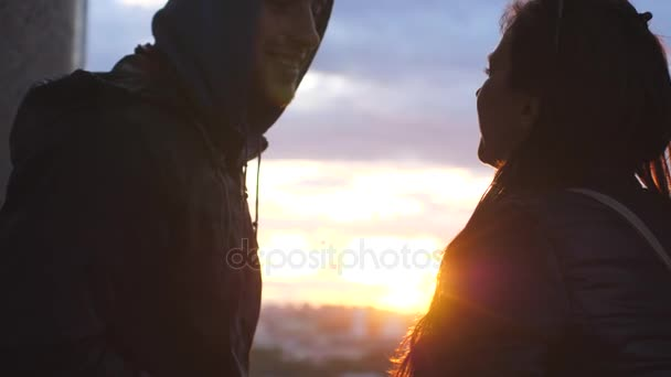 Romantic young couple is kissing on a sunset with sun shining bright behind them on a city horizon. Slow motion. 3840x2160