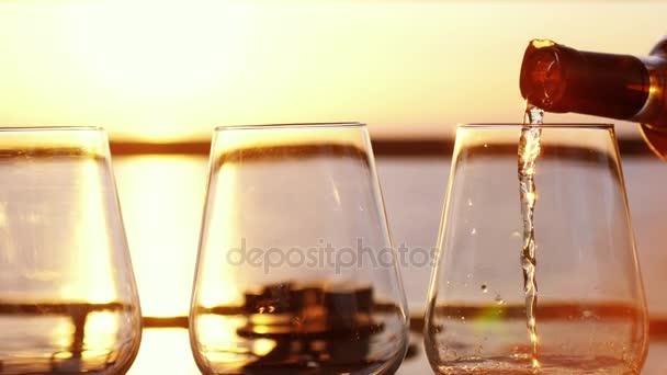 Nalil bílé víno ve skle v pomalém pohybu na úžasný západ slunce s výhledem na moře v plážové restauraci. 3840 x 2160