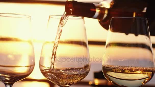 Nalil bílé víno ve čtyřech brýle na úžasný západ slunce u moře v beach café před párty ve zpomaleném filmu. 3840 x 2160, 4k