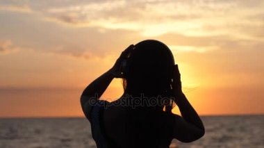 Silhouette of young woman wearing headphones have fun listening music on the beach at amazing sunset in slow motion. 1920x1080