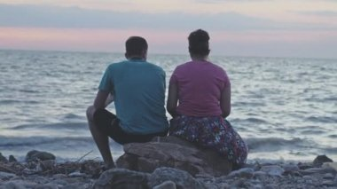 Young couple sits on the stone on the rocky beach, watching the sun set over the ocean in slow motion. 3840x2160