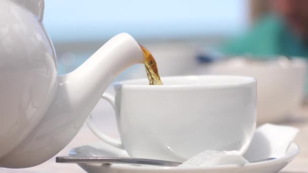 White teapot pouring tea into cup in slow motion in beach cafe by the sea with sunlight. 3840x2160