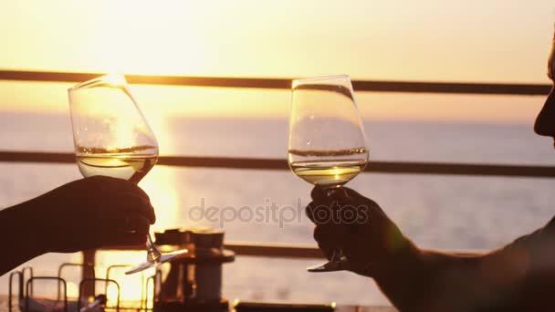Lidé drží sklenku vína, toustu po západu slunce. Kumpáni u bílé víno, opékání. Cinkání. Strana venku. Užívat si čas spolu v pomalém pohybu. 3840 x 2160