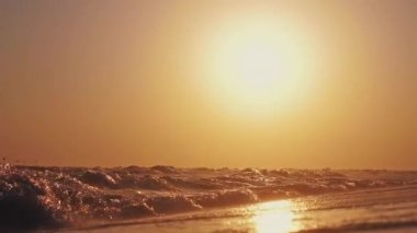 Sunset at the beach background with splashing sea waves in slow motion. 1920x1080