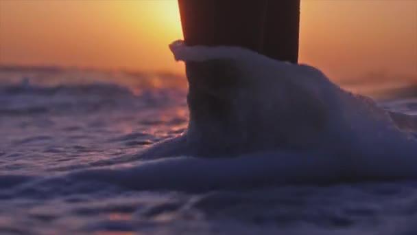 Zblízka se mladá žena nohou stojící nedaleko moře během krásný západ slunce. Zpomalený pohyb. 3840 x 2160