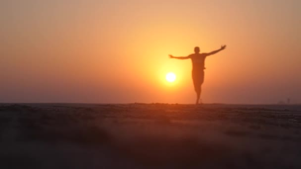 Happy young man wearing cap spinning around with arms raised on beautiful sandy beach at magical golden sunset in slow motion with lens flare effect. 1920x1080 HD