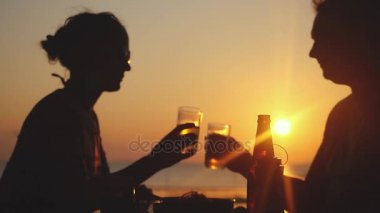 Young happy couple clinking glasses drink beer in beach cafe at amazing sunset in slow motion. 1920x1080
