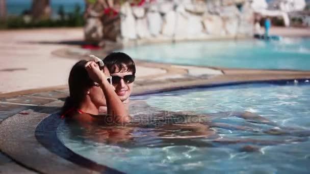 Wellness Spa pár relaxační venkovní bazén luxusní resort Spa ústup. Šťastná mladá žena a muž v sluneční brýle uvolněně opřenou o cestování dovolená dovolenou. 1920 × 1080