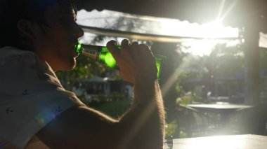 Handsome young man drinking beer in the cafe on beautiful bokeh sunny lights with lens flare effects