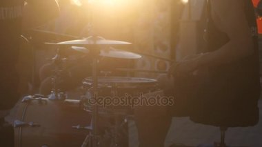Close up of man playing drums on promenade at amazing golden sunset and lens flare effect. slow motion. 3840x2160
