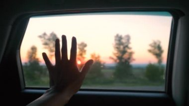 Female hand is playing with sun from car window against beautiful sunset. slow motion. 3840x2160, 4k