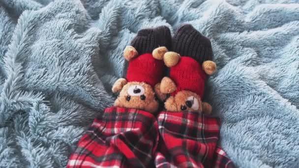Horní pohled na hraní nohy doma v posteli na sobě ponožky s roztomilé medvídky a v pyžamu. Zpomalený pohyb. 3840 x 2160