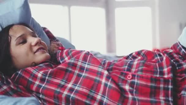 a25aeecdef Mujer morena joven sueño vistiendo pijamas acostado en la cama en su  habitación en cámara lenta. Dólmenes de niña con una manta. cámara lenta.
