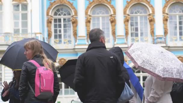 RUSSIA, SAINT PETERSBURG, 20 june 2017, Crowd of people under umbrellas covers in pouring rain stand in line to the Catherine Palace. 4k