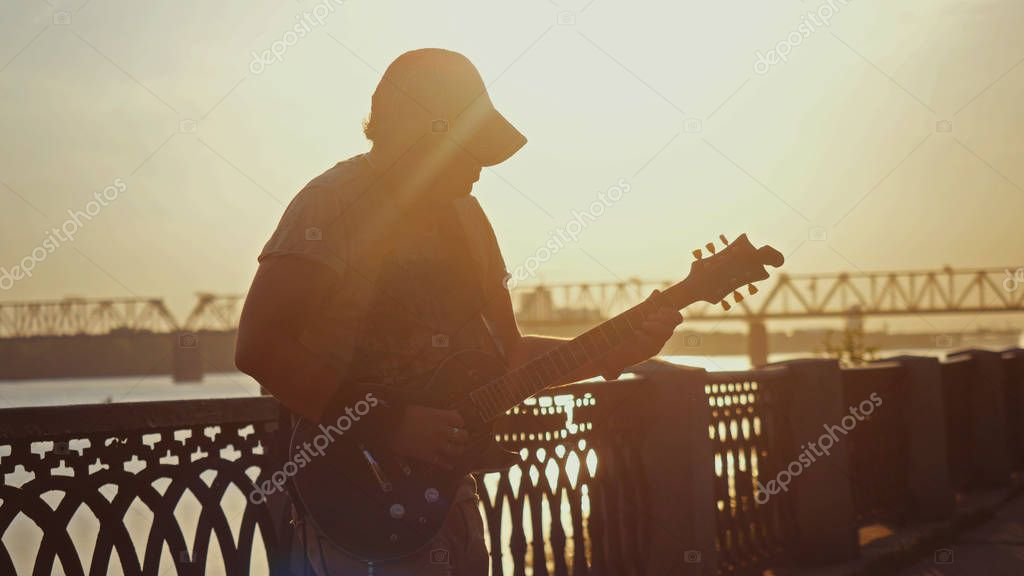 Russia, Novosibirsk, 27 july, 2017. Young caucasian man standing outdoors in promenade and playing guitar at amazing sunset with lens flare effects.