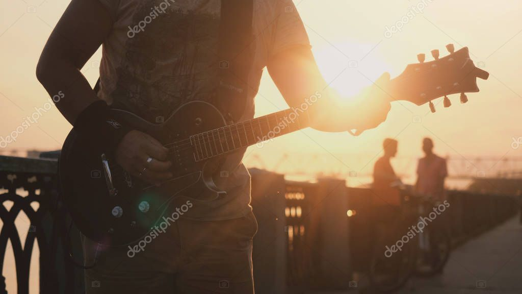 Russia, Novosibirsk, 27 july, 2017. Close up of young caucasian man standing outdoors in promenade and playing guitar at amazing sunset with lens flare effects.