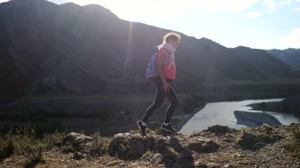 Mladá žena tramp pořizování fotografii s chytrý telefon na horský vrchol útesu s efekty odlesku slunce. 3840 x 2160