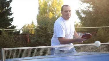 Man beats tennis balls playing table tennis game in the yard in slow motion outdoor close-up in sunny day.