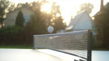 Playing table tennis game in slow motion outdoor in the yard close-up on sunny day.