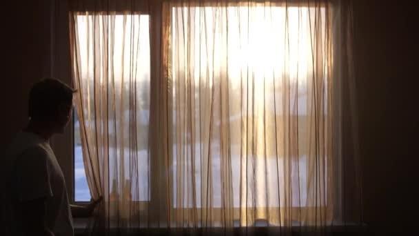 Jonge man opent gordijnen aan heldere zonnige winterdag en kijkt uit ...