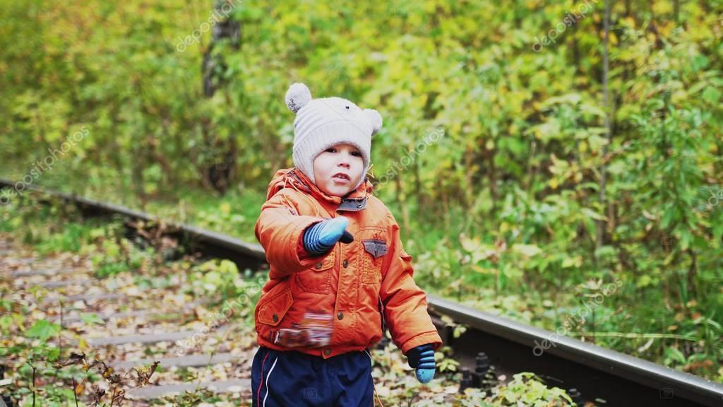 Little boy carefree walks along railway during autumn