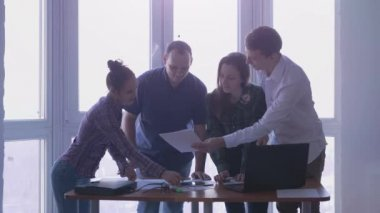 Meeting four elegant people in a stylish office with large panoramic windows at the working place signing deal. 3840x2160