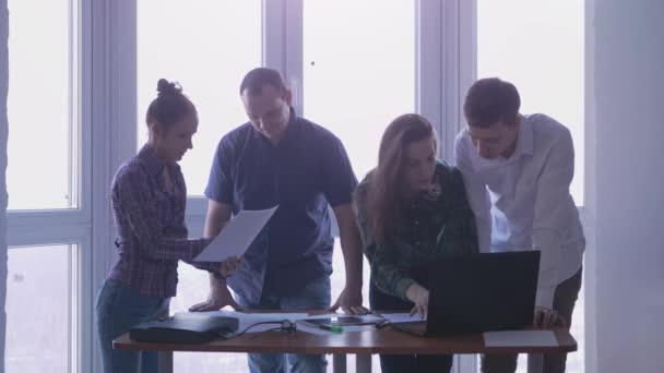 Skupina lidí na pracovišti během firemních setkání v stylové kanceláře s velkým panoramatickým oknem. 3840 x 2160