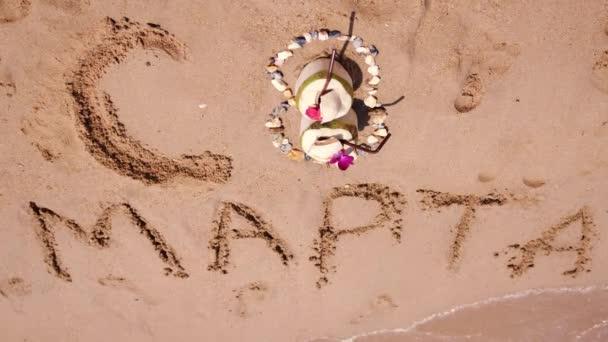 Mezinárodní den Dámské 8.března. 8 číslo z kokosu, kameny a květiny. Text napsaný na písku v tropické pláže. Zpomalený pohyb. 3840 x 2160