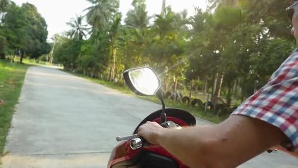 Mladý muž v sluneční brýle turistické jízdy na motorce na tropický slunečný silnici. Zpomalený pohyb. Zblízka. 1920 × 1080