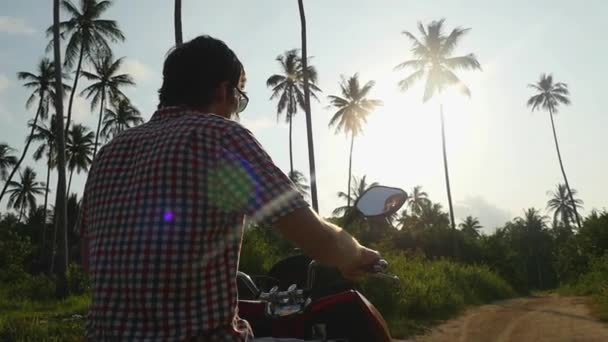 Young handsome man traveler in sunglasses is driving motorbike on tropical sunny road through the sun with lens flare effects. slow motion. 1920x1080