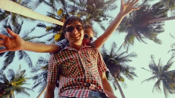 Happy couple in sunglasses enjoying vacation on a tropical beach. A girl on the shoulders of her man having fun. Bottom view on palm trees on the background. Slow motion, 1920x1080