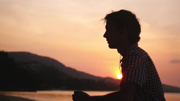 Ein junger gutaussehender Mann mit Kopfhörern läuft bei Sonnenuntergang auf See. Zeitlupe. 1920x1080