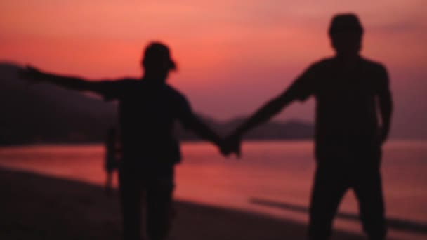 Romantic couple runs on the beach at amazing sunset holding hands. Happy young couple enjoying sunset during travel vacation. slow motion. 1920x1080