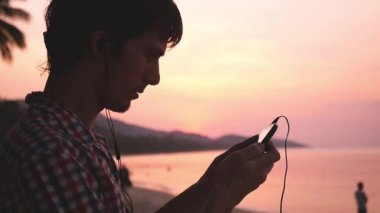 Young handsome man holds mobile phone listens to music on tropical beach during amazing sunset. Slow motion. 1920x1080