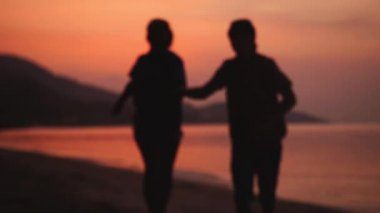 Happy couple run on the beach to the camera during amazing orange sunset holding hands. slow motion. 1920x1080