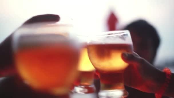 Skupina kumpáni u vína. Lidé kypřicími vinné sklenice aby toast a pití vína. Strana venku na pláži během západu slunce. 1920 × 1080
