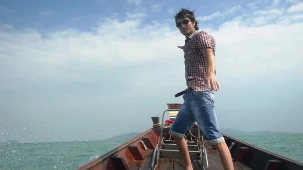 Šťastný mladý pohledný muž v sluneční brýle těší plachetnice na moři stojí na nos dřevěná loď s rukama, slow motion. 1920 × 1080